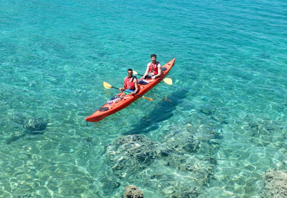 Sea Kayakers floating on aquamarine sea